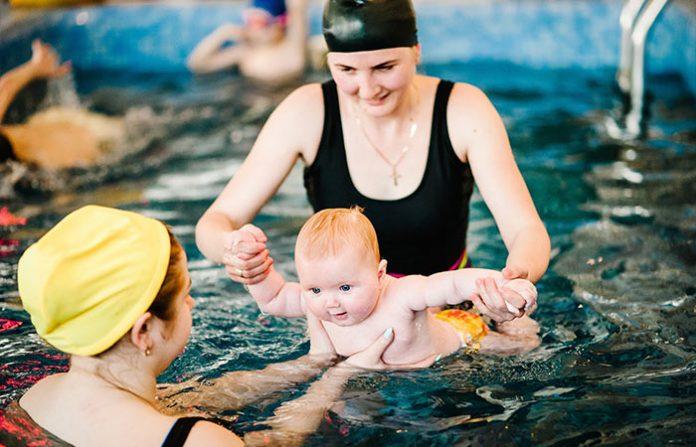 parent helping toddler to swim