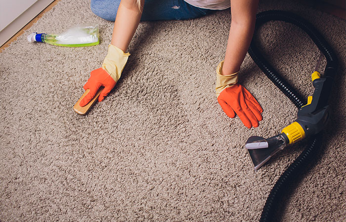 person cleaning carpet using mixture of tools