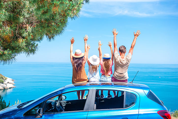Family sitting on top of their blue car